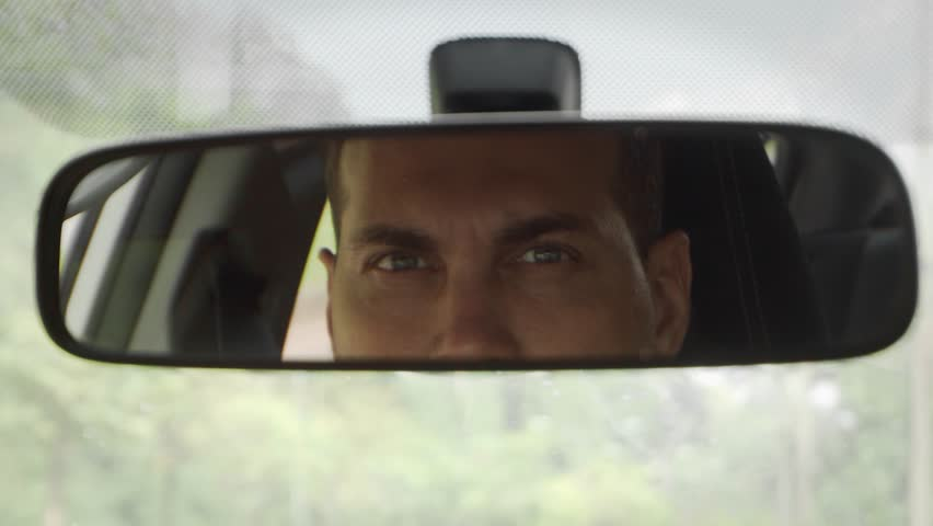 Young Caucasian Man Driving Car Looking in Rear View Mirror