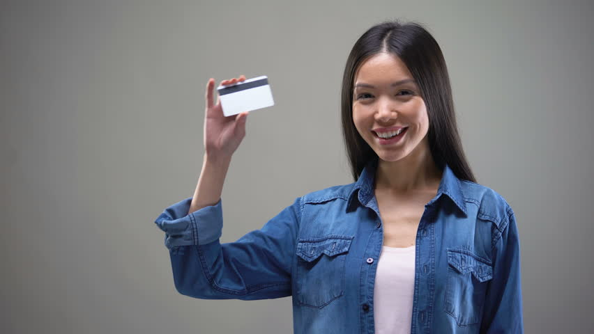 Beautiful Asian woman showing credit card, banking services, payment online | Shutterstock HD Video #1023744655