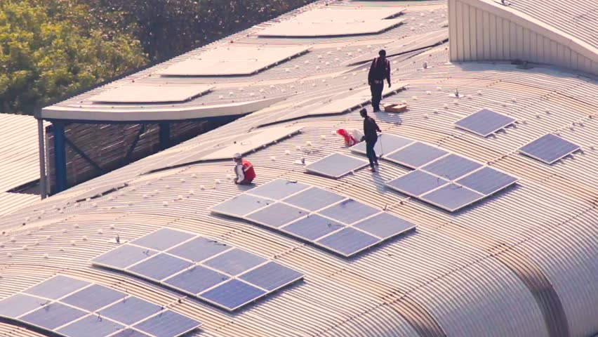 Aerial shot of workmen installing solar panels on the roof of metro station in Noida. These alternate and green power source power projects will help deliver clean energy to the stations. The iron