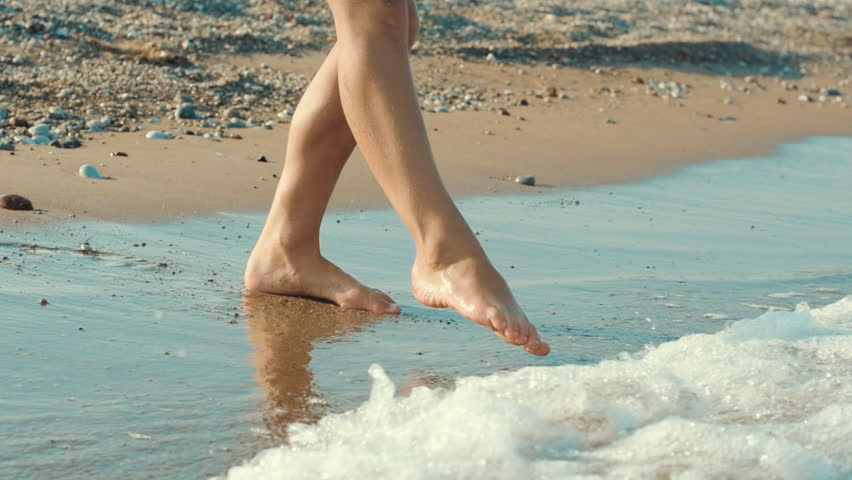 Human legs touching sea water and run away abruptly. Child legs go into sea and run out. Young girl feet on sand beach. Child fear of cold ocean water. Person trying sea water with foot
