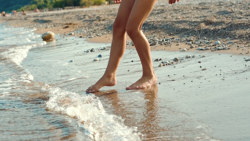 Child trying to bath in cold sea. Person trying water temperature in sea with foot. Girl touching water with foot before bathing in sea. Teenager legs go into sea and running out right away | Shutterstock HD Video #1023781825