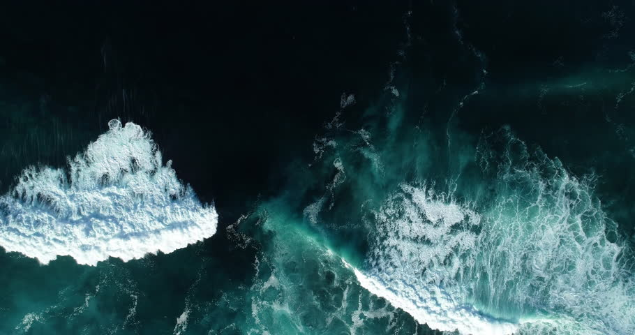 Top down aerial view of giant ocean waves crashing and foaming
