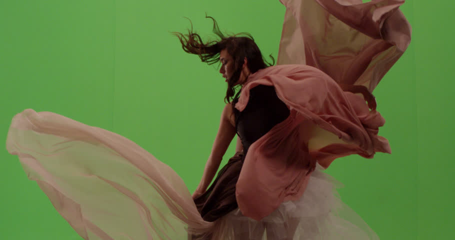 Beautiful fashion model dancer posing against green screen surrounded by flowing fabric | Shutterstock HD Video #1023831262