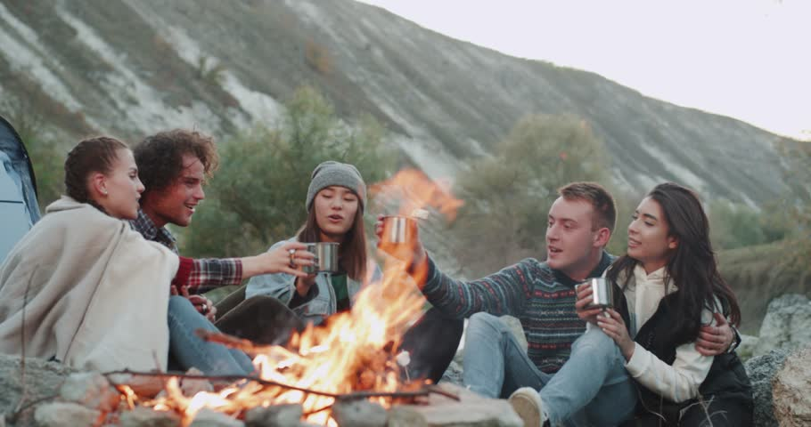 Campfire group of friends sitting down and drinking tea or some hot drinks , from metallic cups , they are very charismatic.