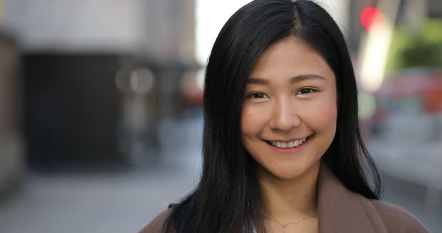 Young Asian woman in city face portrait smile happy