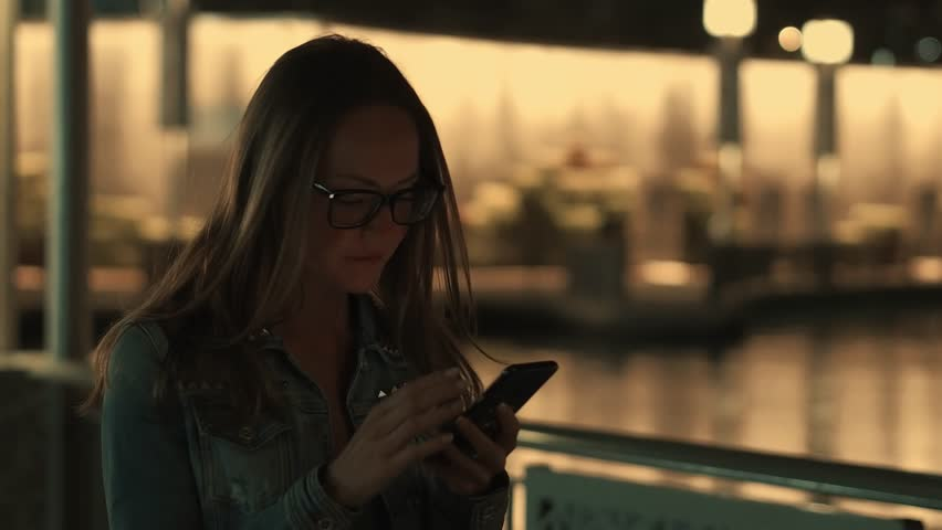 Beautiful young stylish woman walking in the night city streets using modern smartpone, hipster female blogger typing text message on her cellphone | Shutterstock HD Video #1023895249