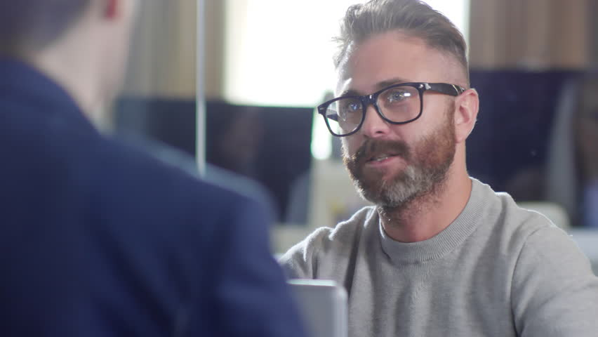 Close up shot of bearded young Caucasian man in glasses and casual clothes having conversation with unrecognizable male colleague seen from his back #1023896857