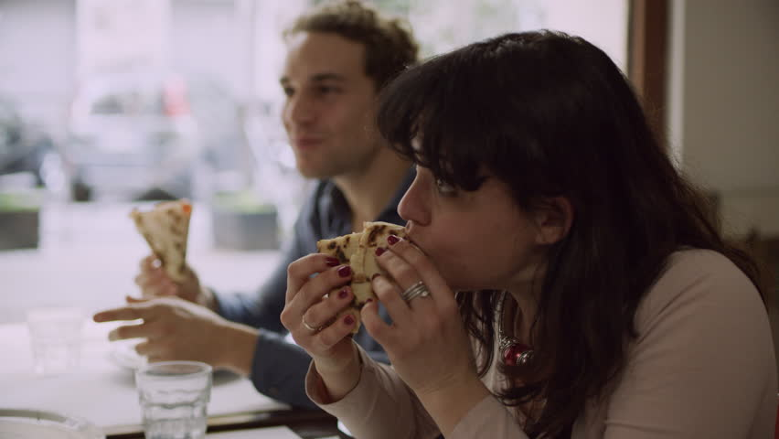 Group of friends eating slices of pizza and talking and laughing in a traditional Italian restaurant in Rome. Medium shot on 8k helium RED camera.