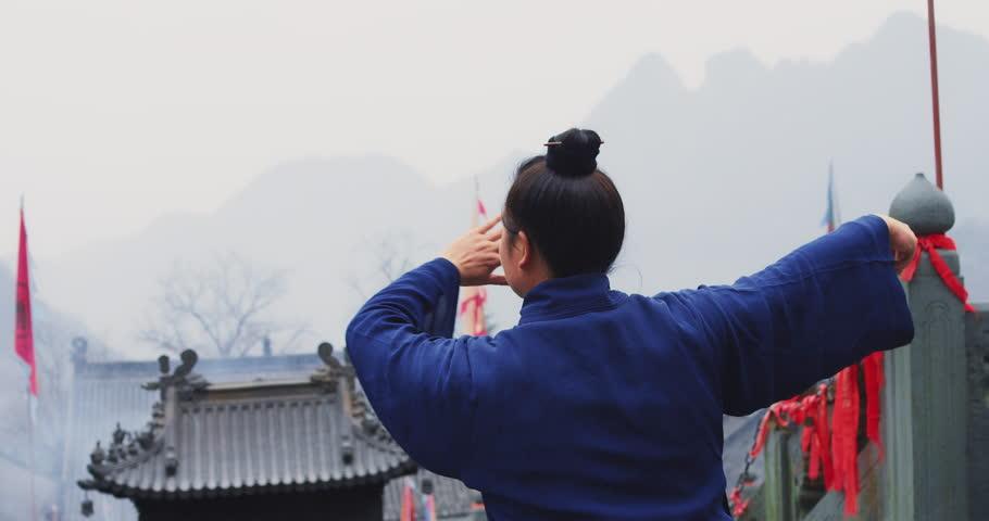 A senior monk of Wudang mountain Monastery in China demonstrates Tai Chi martial arts. Slow motion hand held, Red Cinema camera.