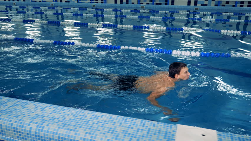 A swimmer with prosthesis training in a pool, side view. | Shutterstock HD Video #1023933461