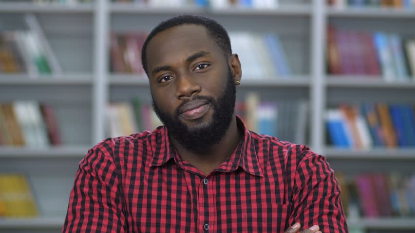 Close-up portrait of joyful african american student in checkered shirt, looking on the video camera. Smiling handsome positive man posing in university library over bookshelves background. #1023934751