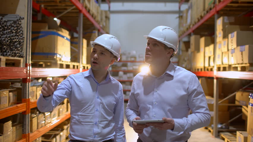 Employees male warehouse workers engineers in hard hat working in logistics center factory construction site, two engineers discussing work with tablet computer. architects businessman man engineer | Shutterstock HD Video #1023937304