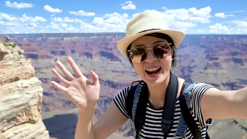 Happy college girl student exchange studying in america sightseeing on summer vacation in Grand Canyon National Park arizona usa. young asian woman waving hand talking video phone call sending kiss