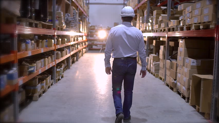 Follow footage of employees male warehouse worker engineer in hard hat working. walking through logistics center warehouse factory construction site logistics architect businessman man builder indoors | Shutterstock HD Video #1023949862