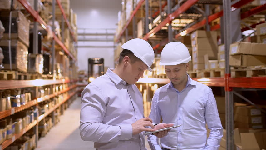 Employees male warehouse workers engineers in hard hats working in logistics center factory construction site. | Shutterstock HD Video #1023949886