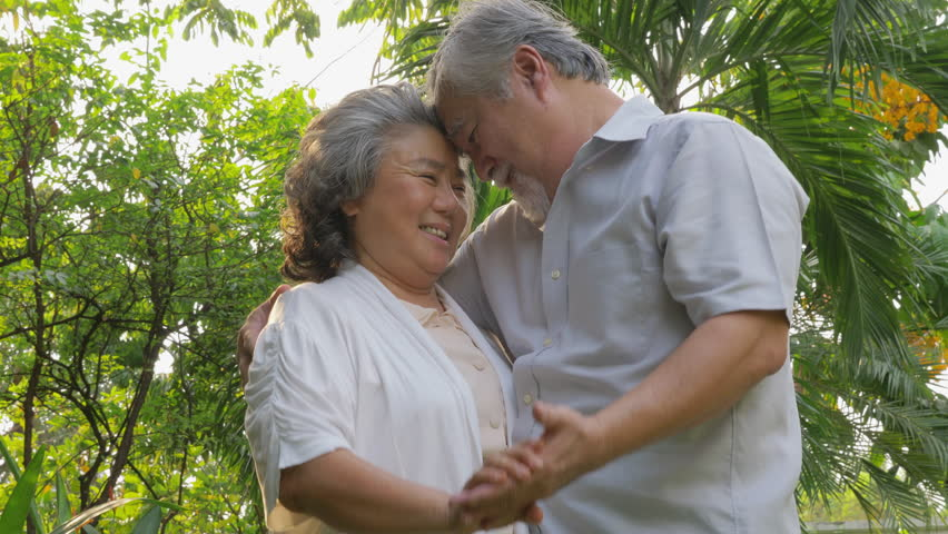 Old senior couple health care active family having fun, asian middle age elderly couple holding hands dancing smile and relax in park nature background, People lifestyle concept. | Shutterstock HD Video #1023950126