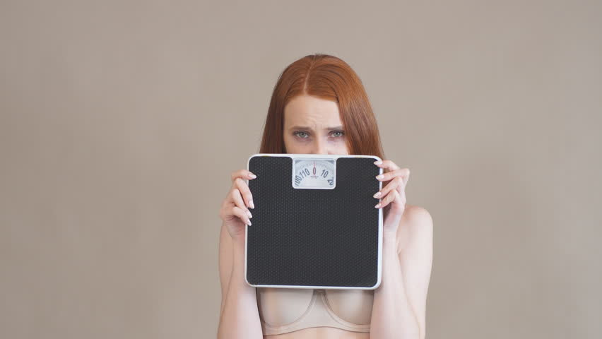 Anorexic girl with a sad face holds the scales and looks at camera, on a gray background.
