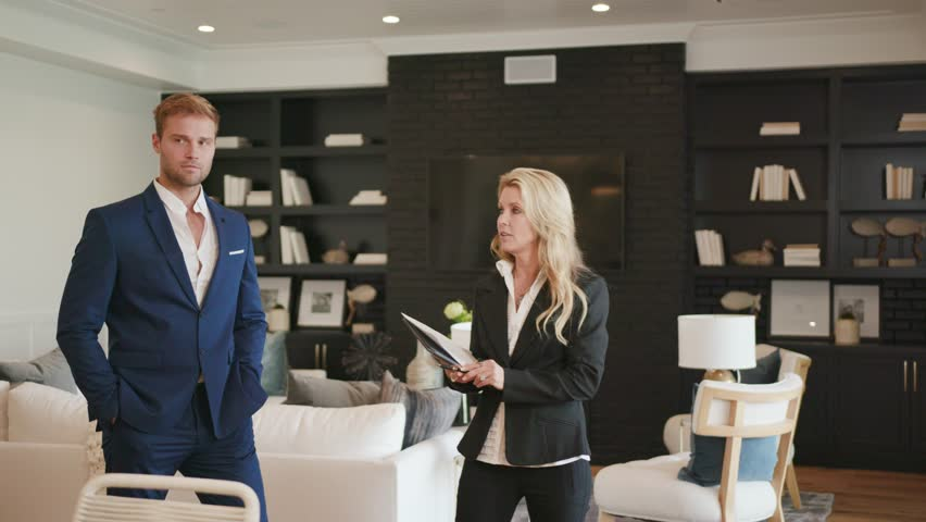 Realtor woman 50s showing a property to young businessman at open house / Selling Real estate  #1023995285