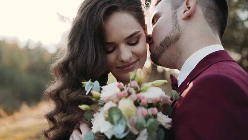 Close-up wedding couple, groom kisses his happy bride's neck. 4K   Shutterstock HD Video #1024025321