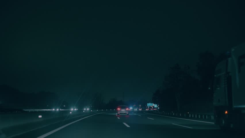 Car rides on busy highway junction, entrance to barcelona city at nigh time. Dark motorway lit up with stop lights of cars and other vehicles. Concept driving in rain or at night