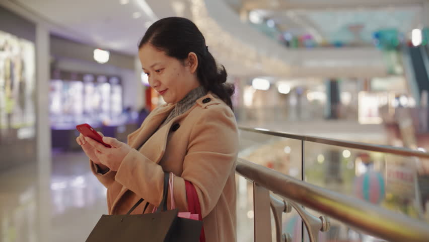 Chinese woman using smart phone in shopping mall in shenzhen,young woman texting through smart phone and smiling in street #1024035974