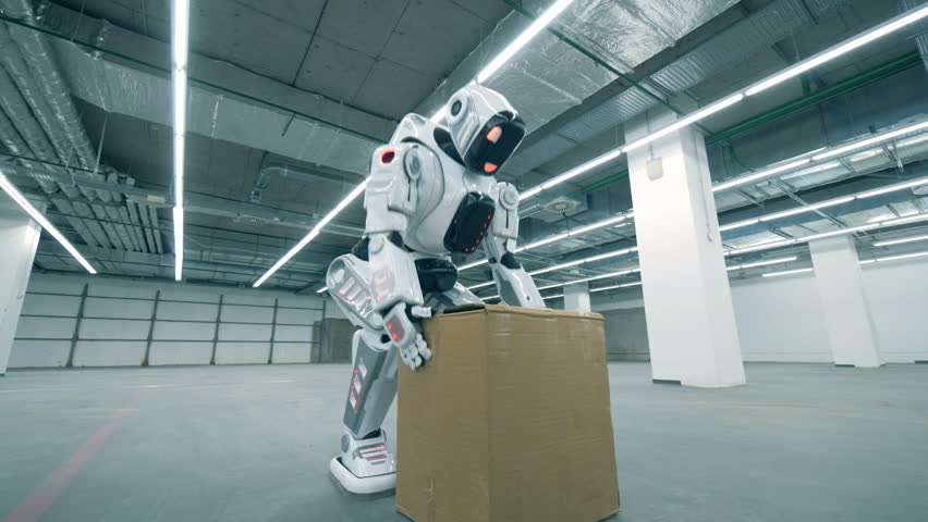 Empty storage unit with a robot lifting a carton box and carrying it | Shutterstock HD Video #1024036979