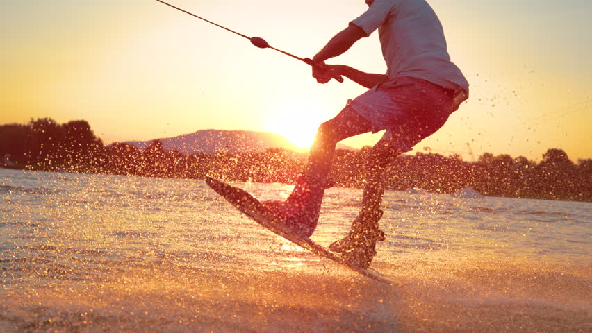 SLOW MOTION, TIME REMAP, SUN FLARE, CLOSE UP: Cool surfer dude does 180 ollie while wakeboarding on a sunny summer evening. Cinematic shot of a cheerful man wakeboarding in the cool cable wake park