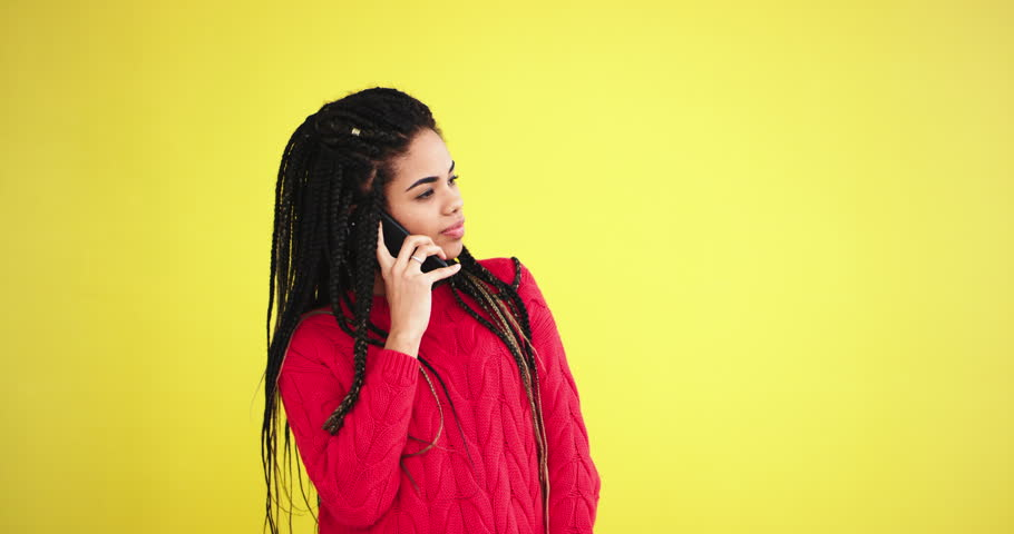 Young african woman have a conversation using her smartphone , taking in front of the camera in the studio with a yellow background wall | Shutterstock HD Video #1024056149