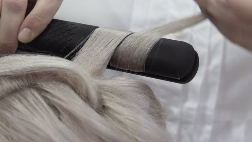 Close-up Of The Hand Of A Master Hairdresser Doing Styling Beautiful Curls With The Help Of Iron Curling On Blond Long Hair. Concept Of Beauty Salon And Hairdresser | Shutterstock HD Video #1024072292