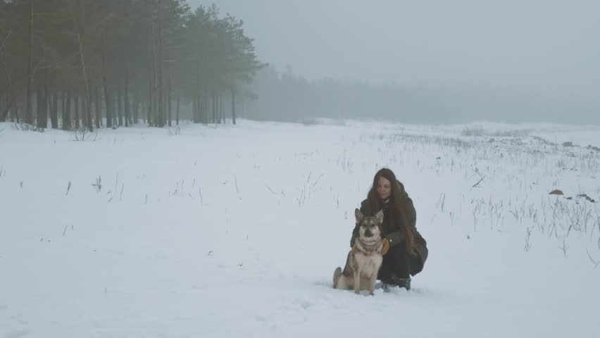 Winter snow vacation. Young woman with long hair stroking her mixbreed dog near the frozen river, foggy cloudy weather in the forest near river. Slow motion . | Shutterstock HD Video #1024077737