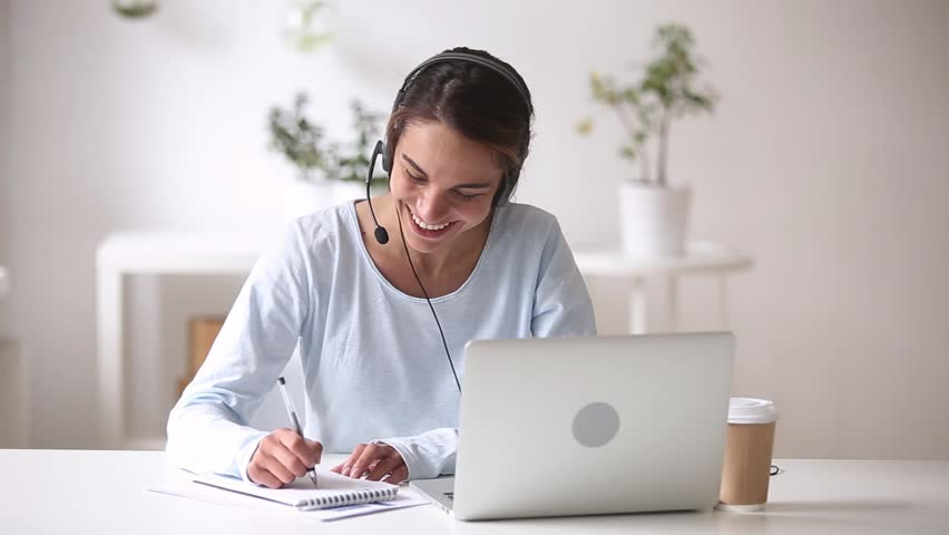 Happy woman in headphones speaking by webcam at webinar training look at laptop make notes, girl student talking by video conference call, online teacher teaching consulting client e-coaching concept