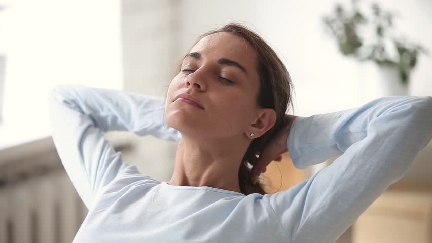 Relaxed young woman with happy face eyes closed breathing fresh air chilling with hands behind head, calm smiling girl dreaming enjoying peace of mind meditating lounging on stress free day concept | Shutterstock HD Video #1024093457