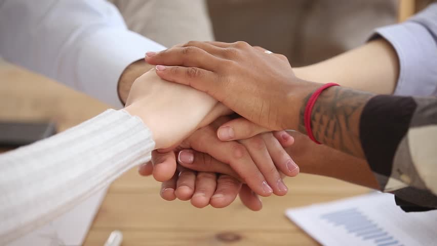 Diverse people stacking hands together in pile, multi ethnic students sales team engaged in corporate teambuilding connected in teamwork help support coaching training unity concept, close up view