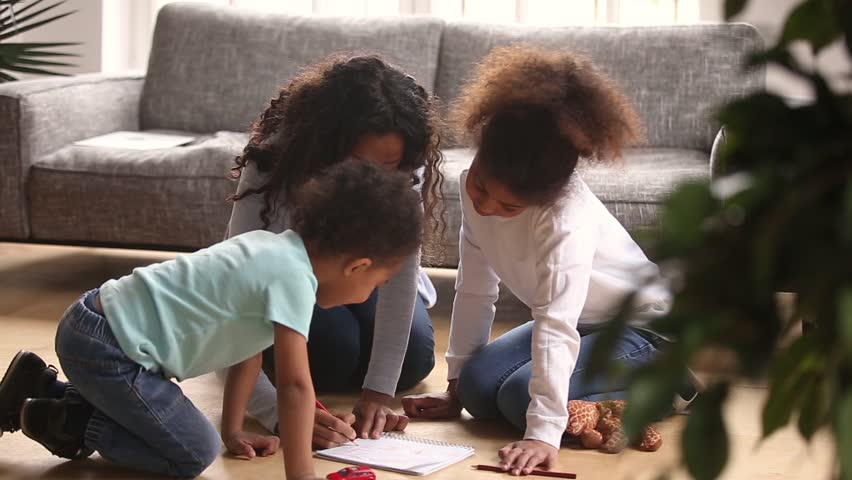 Caring african mother baby sitter drawing with colored pencils teaching two little kids sitting on warm floor at home, loving black mom helping children play together, creative family hobby activity