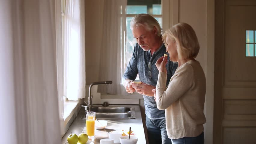 Happy loving senior mature couple having fun preparing healthy breakfast food in kitchen, playful old aged smiling family talking laughing cooking cutting feeding each other together at home #1024093946