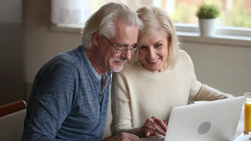 Happy old middle aged couple using laptop talking together doing online shopping, senior mature retired family reading discussing internet computer news, choosing travel offer on website at home Royalty-Free Stock Footage #1024093949