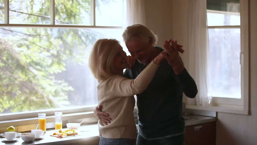Happy mature senior couple dancing laughing in the kitchen, beautiful romantic middle aged older grandparents relaxing having fun together at home celebrating anniversary enjoy care love tenderness #1024093952
