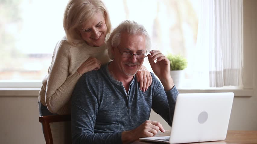 Happy senior middle aged couple laughing talking embracing using laptop together looking at computer screen, smiling older mature family enjoying watching funny video or making online call at home  Royalty-Free Stock Footage #1024093958