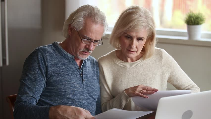 Serious senior mature couple talking disputing holding paper bills checking finances expenses, older middle aged family reading bank loan payments documents at home worried about debt money problems