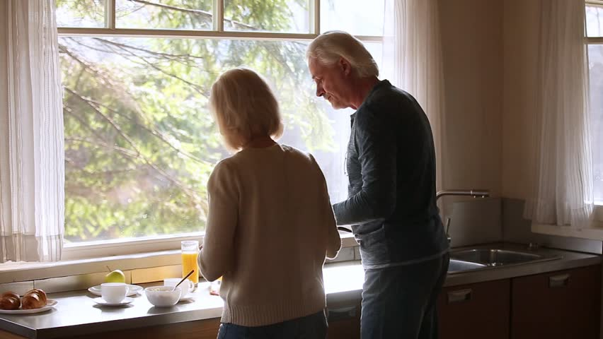 Rear back view at senior middle aged family couple enjoying helping cooking together in the morning, loving older husband and mature wife talking preparing healthy breakfast in the kitchen at home