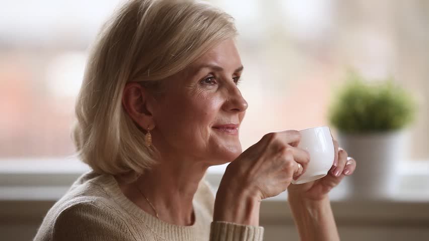 Calm happy mature old woman sitting alone holding cup enjoying aroma morning hot coffee and dreaming, beautiful dreamy senior middle aged lady drinking tea relaxing at home on pleasant leisure day | Shutterstock HD Video #1024093976