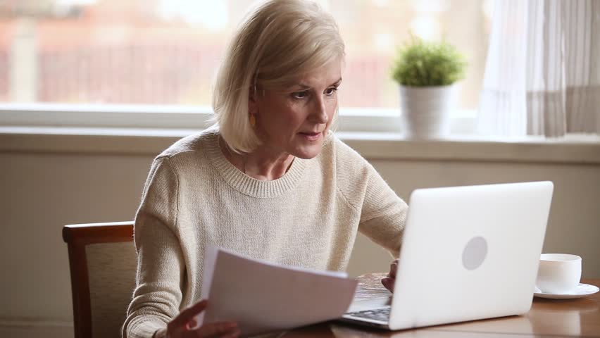 Happy senior middle aged woman holding financial documents using laptop for internet banking, smiling old mature lady paying bill with online application on laptop working on computer doing paperwork Royalty-Free Stock Footage #1024093985