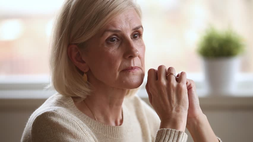 Sad thoughtful anxious mature senior woman feeling lonely worried concerned about problems, pensive depressed upset middle aged widow lady sitting alone grieving thinking of getting older loneliness Royalty-Free Stock Footage #1024093988