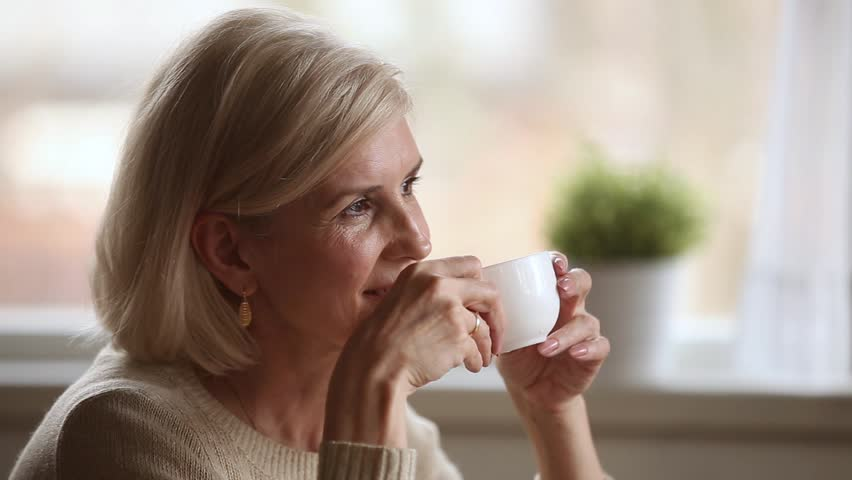 Dreamy happy middle aged mature woman looking away drinking morning coffee or tea at home, smiling senior old lady holding cup relaxing with positive thoughts dreaming enjoying pleasant memories Royalty-Free Stock Footage #1024093994