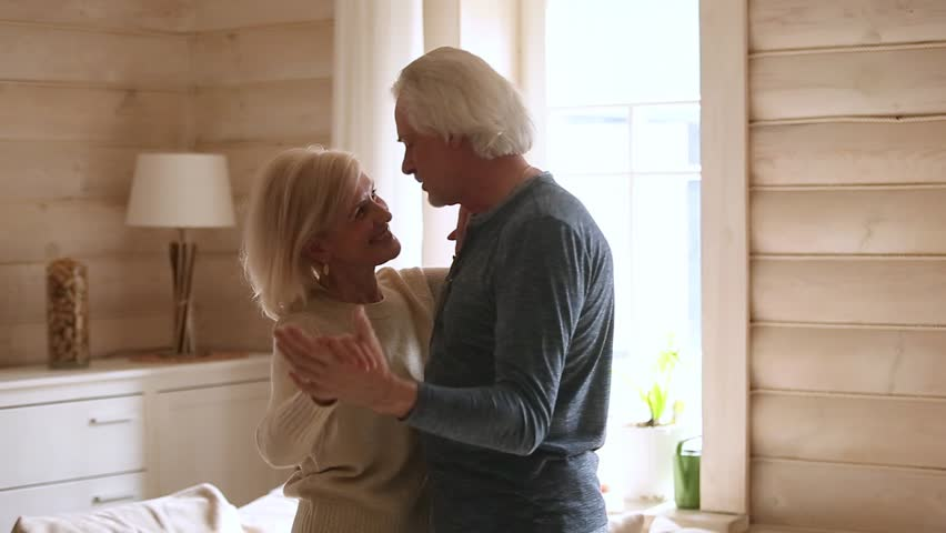 Happy senior romantic couple dancing in modern country house living room, loving old middle aged family grandparents husband and wife enjoy tender moment celebrating anniversary relaxing together Royalty-Free Stock Footage #1024094003