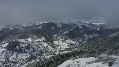 Village with buildings covered with snow. Aerial view among the clouds