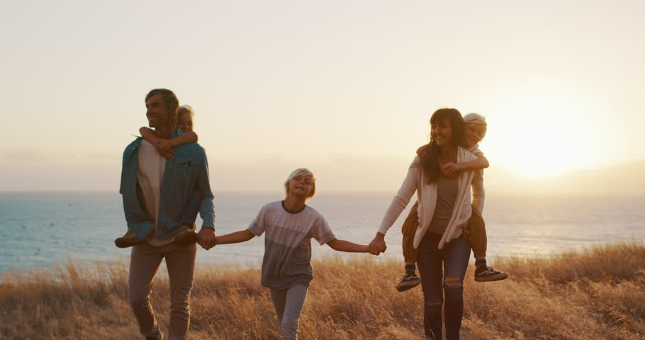 Happy smiling family holding hands walking through golden field at sunset by the ocean, piggy back ride #1024117913