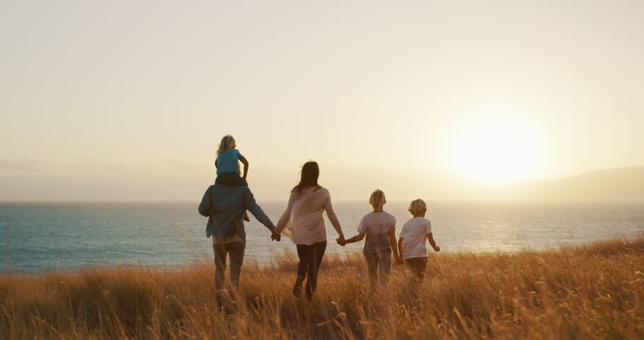 Happy family walking in golden field and looking out to the sunset together by the ocean #1024117916