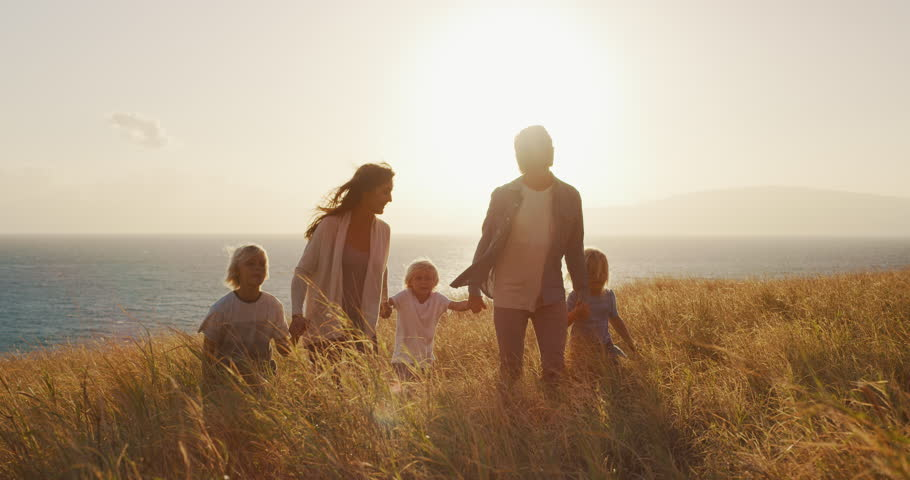 Happy smiling family swinging child into the air in golden fields by the ocean at sunset Royalty-Free Stock Footage #1024117919