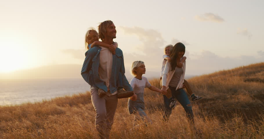 Happy smiling family holding hands walking through golden field at sunset by the ocean, piggy back ride | Shutterstock HD Video #1024118153
